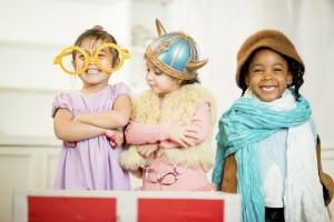 Little girls dressed in theatrical costume laughing and smiling together.